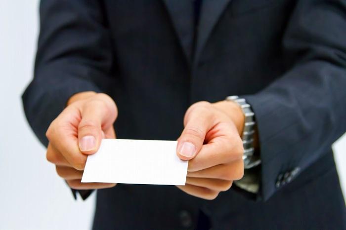 名刺を出すスーツ姿の男性