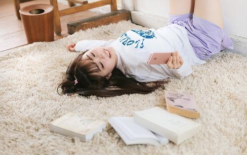 部屋で寝転がる女子大生